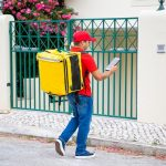 Courier with isothermal food backpack consulting tablet, checking address and walking to gate and doorbell. Communication or delivery service concept